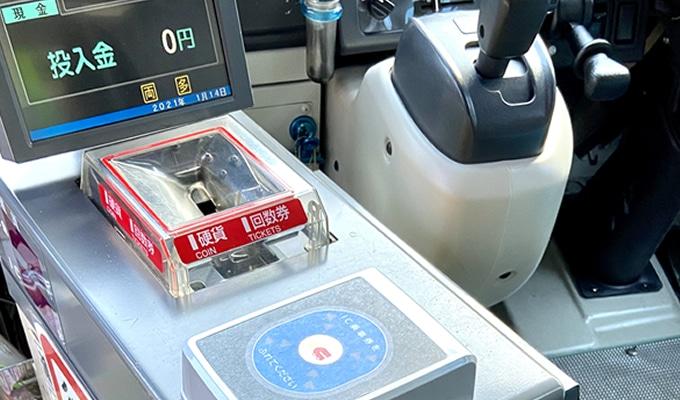 目的地にバスが停車後、運賃と整理券を運賃箱にいれる